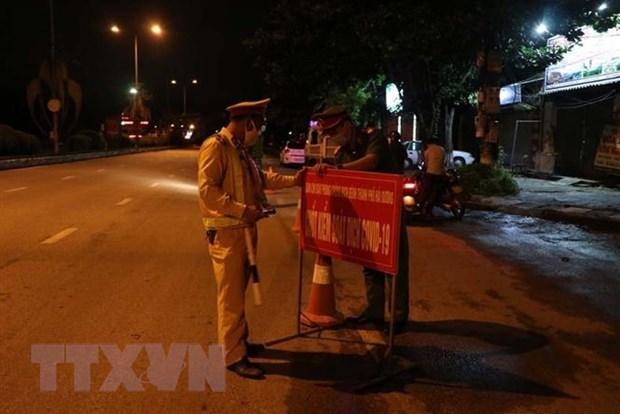 Các chiến sĩ công an trực tại chốt vị trí cuối đường Nguyễn Lương Bằng gần tiếp giáp với quốc lộ 5 lúc 0 giờ 20 phút ngày 14/8. (Ảnh: Mạnh Minh/TTXVN)
