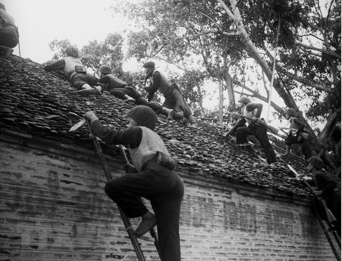 """Sau Cách mạng Tháng Tám, trước dã tâm của thực dân Pháp quay trở lại, dùng vũ lực hòng đặt lại ách thống trị trên đất nước ta một lần nữa, toàn dân tộc Việt Nam đã nhất tề đứng lên kháng chiến, chống thực dân Pháp xâm lược theo Lời kêu gọi toàn quốc kháng chiến ngày 19/12/1946 của Chủ tịch Hồ Chí Minh với ý chí """"Quyết tử cho Tổ quốc quyết sinh,"""" """"thà hi sinh tất cả chứ nhất định không chịu mất nước, nhất định không chịu làm nô lệ"""". Trong ảnh: Các chiến sỹ Vệ Quốc đoàn chiến đấu kiên cường, bảo vệ từng ngôi nhà, tấc đất của Thủ đô trong những ngày đầu Toàn quốc kháng chiến, tháng 12/1946. (Ảnh: Tư liệu TTXVN)"""