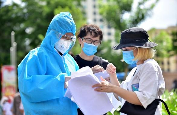 Nhân viên y tế hướng dẫn công dân nước ngoài đang sống tại Việt Nam các bước làm thủ tục để vào khu vực tiêm