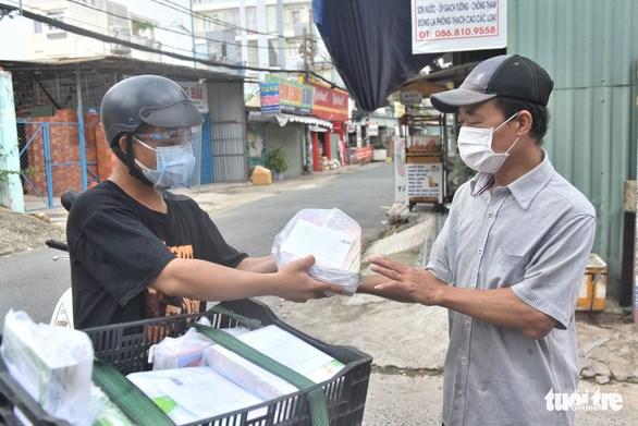 Nhân viên Công ty CP đầu tư và phát triển giáo dục Phương Nam (Nhà xuất bản Giáo Dục Việt Nam) giao sách tận nhà cho phụ huynh ở Gò Vấp (TP.HCM) chiều 30/8 - Ảnh: DUYÊN PHAN