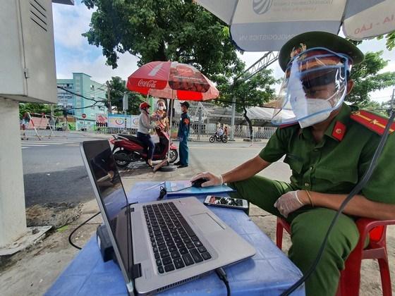 Cán bộ tại chốt kiểm tra qua máy tính sau khi người dân quét mã QR qua hệ thống camera tự động. Ảnh: CHÍ THẠCH