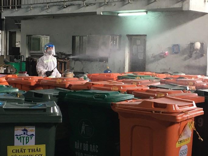 Công nhân xịt khuẩn các thùng rác y tế tại công trường xử lý rác ở Đông Thạnh, huyện Hóc Môn