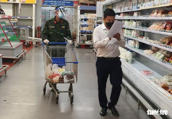 Cán bộ phường cùng bộ đội đi chợ giúp người dân ở siêu thị tại TP Thủ Đức - Ảnh: MINH HÒA