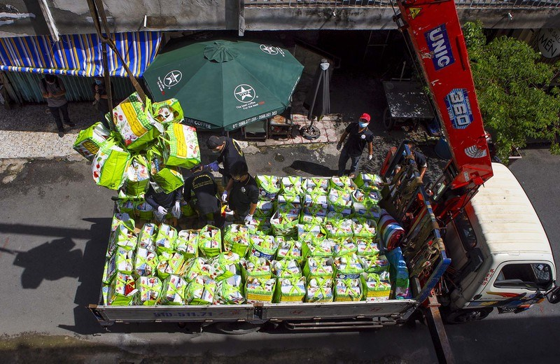 Mỗi xe chở khoảng 400 phần quà, đặt giữa 2 block chung cư, để chuyển lên các hộ dân lầu 1 đến lầu 4 bằng cẩu gắn rơ móc.
