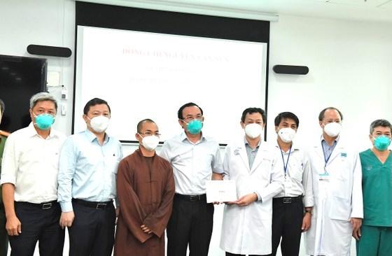 Bí thư Thành ủy TPHCM Nguyễn Văn Nên tặng quà động viên lực lượng y bác sĩ, các tình nguyện viên tại Bệnh viện Hồi sức Covid-19. Ảnh: VIỆT DŨNG