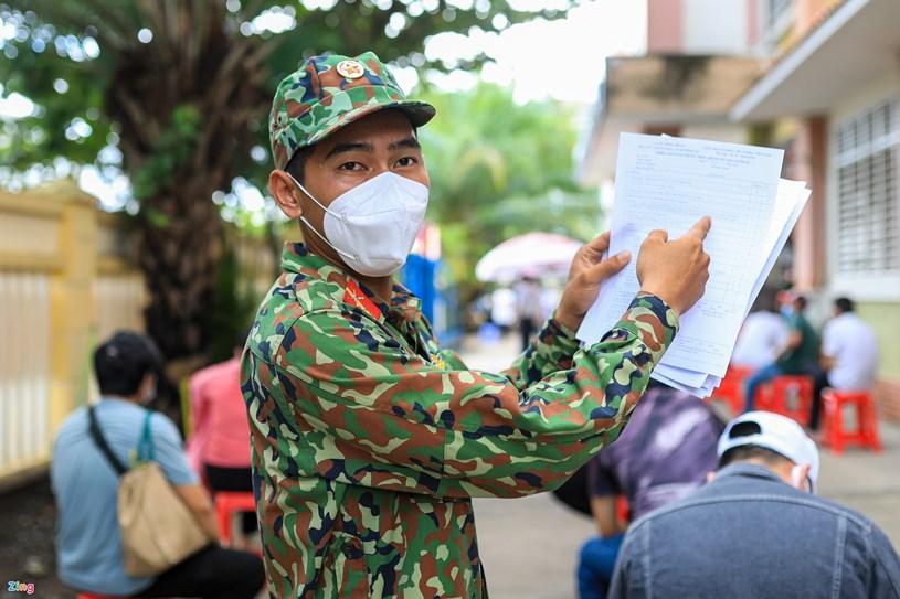 Bên trong trường học, người dân được lực lượng chức năng phát giấy và hướng dẫn điền thông tin cá nhân, khai báo y tế