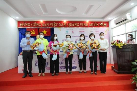 Tổng Biên tập Báo SGGP Tăng Hữu Phong tặng hoa tri ân các đơn vị ủng hộ chương trình. Ảnh: DŨNG PHƯƠNG