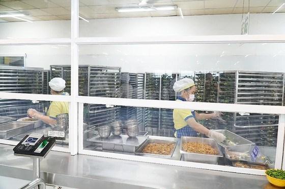 Bảo mẫu tại bếp ăn tập thể một trường học trên địa bàn TPHCM chuẩn bị suất ăn trưa cho học sinh