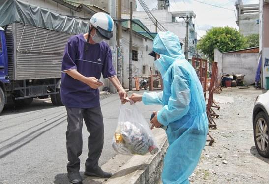 Đội hình SOS của Trung tâm An sinh TP HCM trao túi an sinh cho người dân khó khăn, công nhân mất việc ở quận Bình Tân. Ảnh: Nguyễn Phan