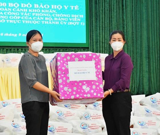 Phó Trưởng ban Thường trực Ban Dân vận Thành ủy TPHCMNguyễn Thị Bạch Mai (phải) trao tặng đồ bảo hộ y tế cho huyện Bình Chánh. Ảnh: VIỆT DŨNG