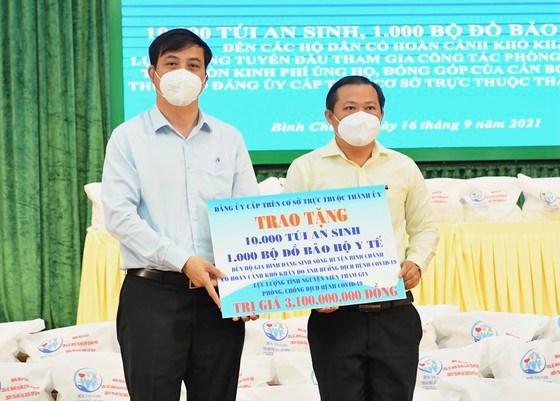 Phó Chủ tịch UBND TPHCM Lê Hòa Bình trao tặng túi an sinh và đồ bảo hộ y tế cho huyện Bình Chánh. Ảnh: VIỆT DŨNG