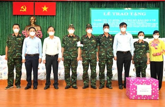 Phó Chủ tịch UBND TPHCM Lê Hòa Bình cùng lãnh đạo huyện Bình Chánh tặng túi an sinh và đồ bảo hộ y tế cholực lượng y bác sĩ quân y đang làm nhiệm vụ tại huyện Bình Chánh. Ảnh: VIỆT DŨNG