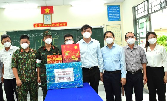 Phó Chủ tịch UBND TPHCM Lê Hòa Bình tặng quà cho lực lượng quân y, tình nguyện viên đang làm nhiệm vụ tại các trạm y tế lưu động trên địa bàn huyện Bình Chánh. Ảnh: VIỆT DŨNG