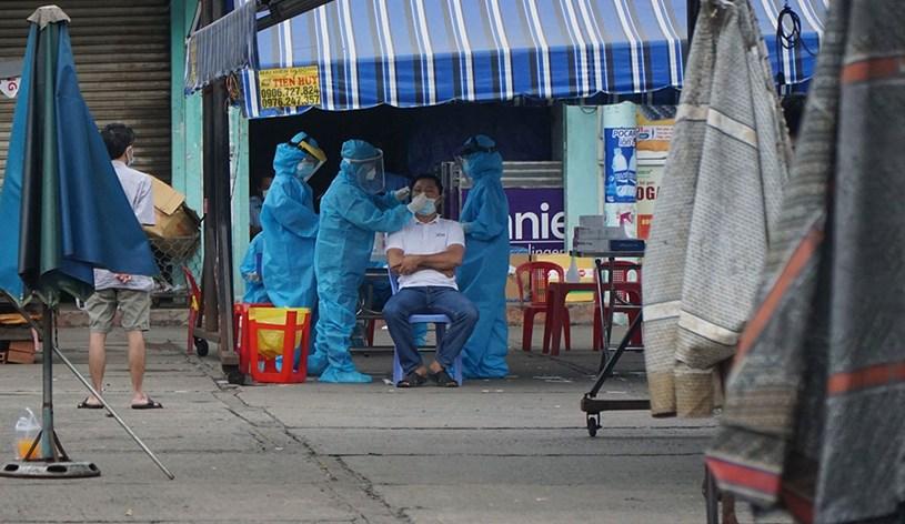 Lực lượng chức năng lấy mẫu xét nghiệm sau khi phát hiện ca nhiễm Covid-19 tại chợ Sơn Kỳ, Q.Tân Phú, TP.HCM. Ảnh: Báo Thanh Niên