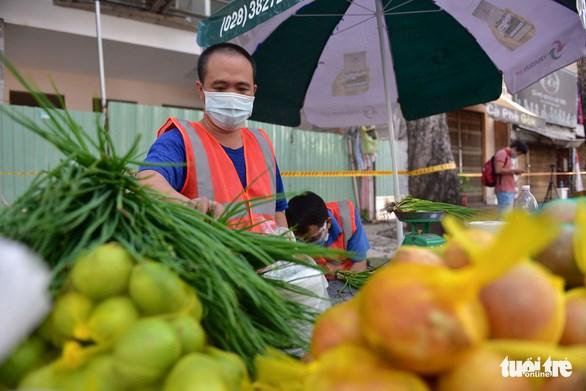 Anh Bùi Thế Long (nhân viên Trung tâm thương mại dịch vụ An Đông) hỗ trợ bán hàng tại chợ lưu động - Ảnh: NGỌC PHƯỢNG
