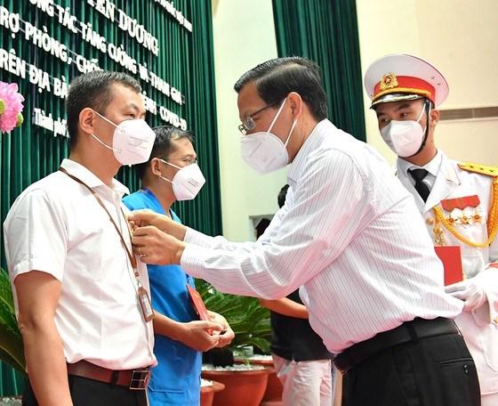 Đồng chí Phan Văn Mãi trao tặng Huy hiệu TPHCM cho các bác sĩ tham gia phòng chống dịch COVID-19 trên địa bàn TPHCM. Ảnh: VIỆT DŨNG