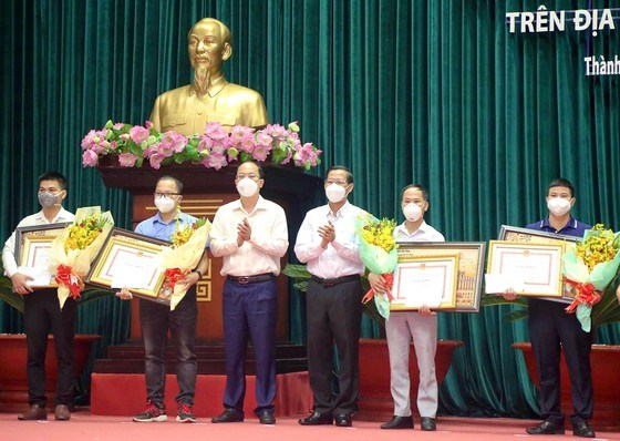 Chủ tịch UBND TPHCM Phan Văn Mãi và Phó Bí thư Thành uỷ TPHCM Nguyễn Hồ Hải tặng Bằng khen cho các đoàn công tác. Ảnh: VIỆT DŨNG