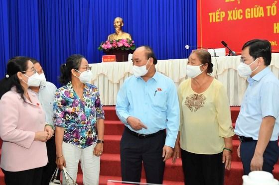 Chủ tịch nước Nguyễn Xuân Phúc trò chuyện với các đại biểu, cử tri bên lề buổi tiếp xúc cử tri sáng 11/10. Ảnh: VIỆT DŨNG