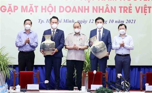 Chủ tịch nước Nguyễn Xuân Phúc tặng quà lưu niệm cho Hội doanh nhân trẻ Việt Nam nhân dịp Ngày Doanh nhân Việt Nam 13/10. (Ảnh: Thống Nhất/TTXVN)