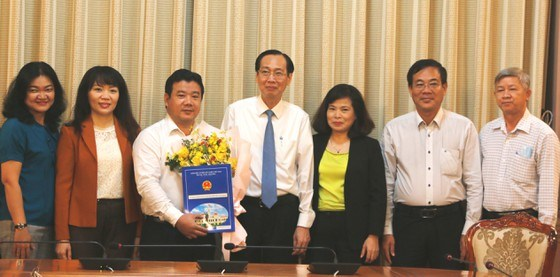 Phó Chủ tịch Thường trực UBND TPHCM Lê Thanh Liêm trao quyết định và tặng hoa chúc mừng tân Phó Giám đốc Sở Tài chính TPHCM Nguyễn Trần Phú