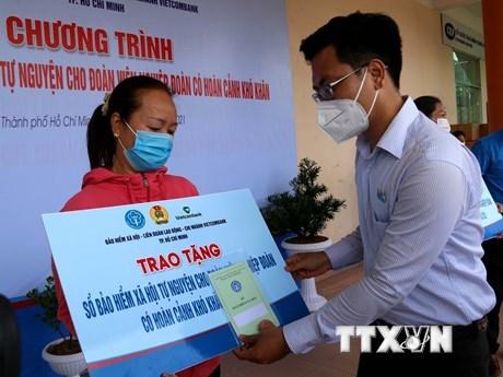 Lãnh đạo Quận ủy quận Tân Phú trao sổ bảo hiểm cho đoàn viên nghiệp đoàn có hoàn cảnh khó khăn ở quận Tân Phú. (Ảnh: Thanh Vũ/TTXVN)