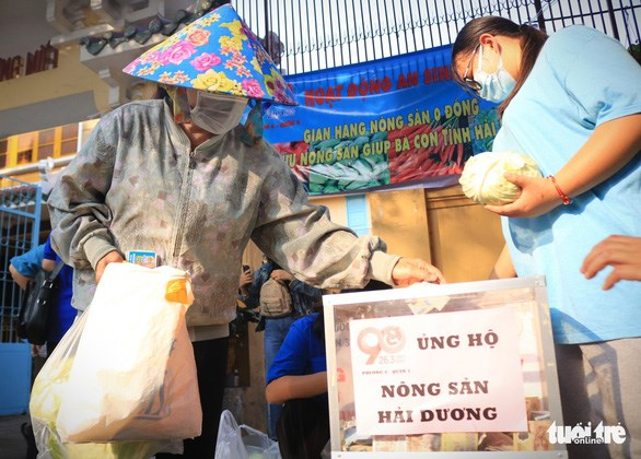 """Người dân nhận bắp cải và gửi tiền ủng hộ tùy khả năng để nhóm tiếp tục """"giải cứu"""" nông sản cho bà con Hải Dương - Ảnh: NHẬT THỊNH"""