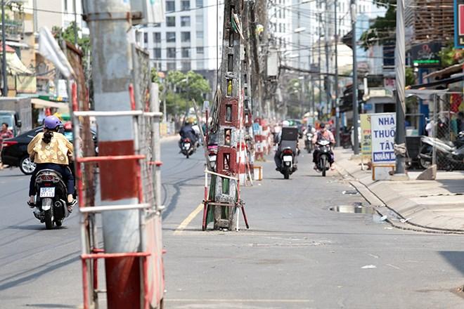 Các trụ điện được sơn vạch đỏ, trắng và dùng cây, lưới rào xung quanh để cảnh báo người dân đi đường. Ảnh: báo Dân Việt