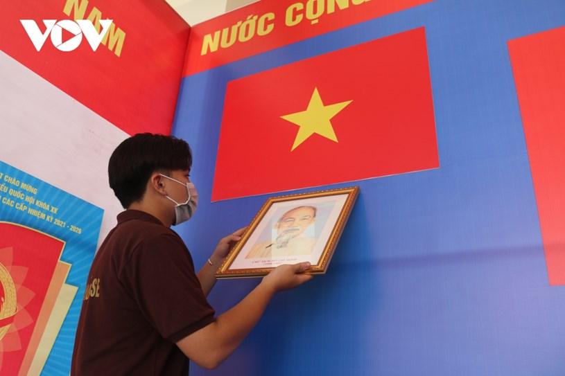 Nhiều điểm bầu cử đang hoàn tất các công đoạn chuẩn bị. Trong ảnh, một bạn trẻ đang treo ảnh Bác Hồ, trang trí phông khu vực bỏ phiếu.