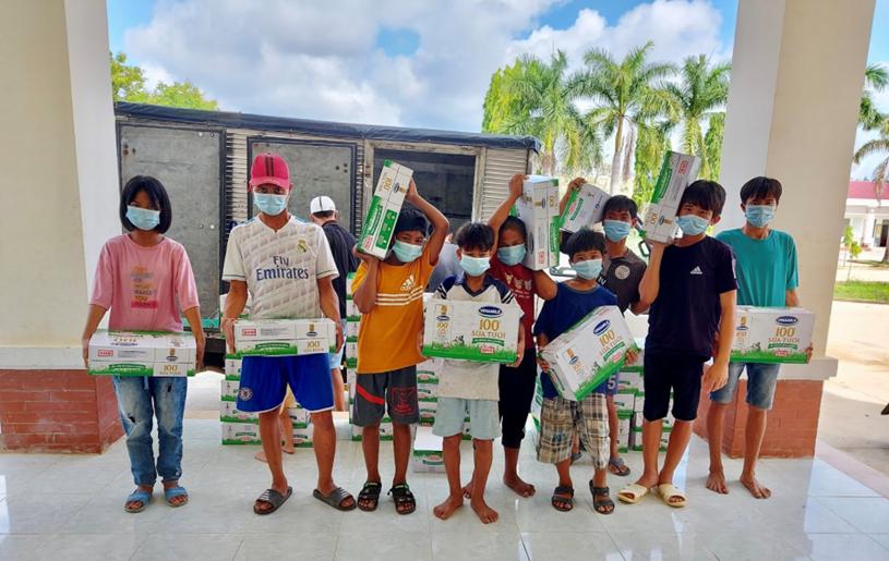 Hình ảnh đáng yêu của các em tại Trung tâm Bảo trợ và Công tác Xã hội Kon Tum đang phụ các thầy cô chuyển sữa vào trong.