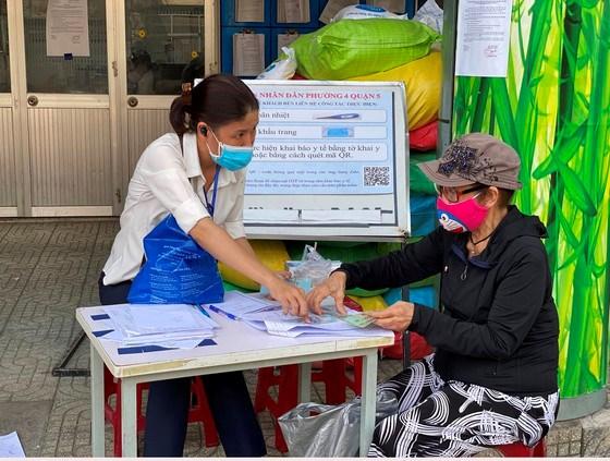 Chi trả tiền hỗ trợ tới người lao động tự do tại quận 5. Ảnh: CAO THĂNG