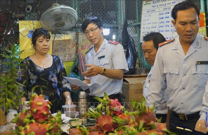 Cán bộ Ban Quản lý an toàn thực phẩm Thành phố Hồ Chí Minh kiểm tra trái cây, hóa đơn mua bán tại Chợ nông sản Thủ Đức/TTXVN