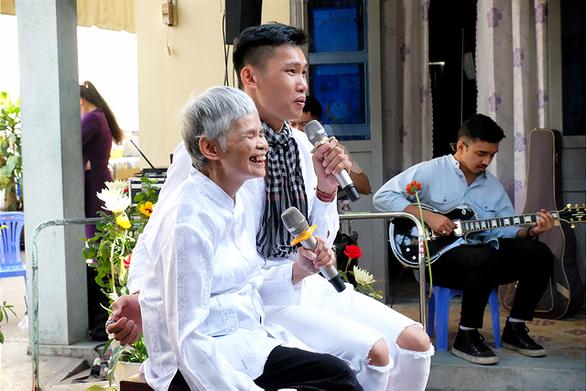 Cụ bà Mỹ Lệ (75 tuổi) hát những bài hát mà bà từng đi hát khi còn đi bán vé số. Mặc dù không còn nhìn thấy nữa nhưng cụ bà đã cười rất tươi - ẢNH: VŨ THỦY