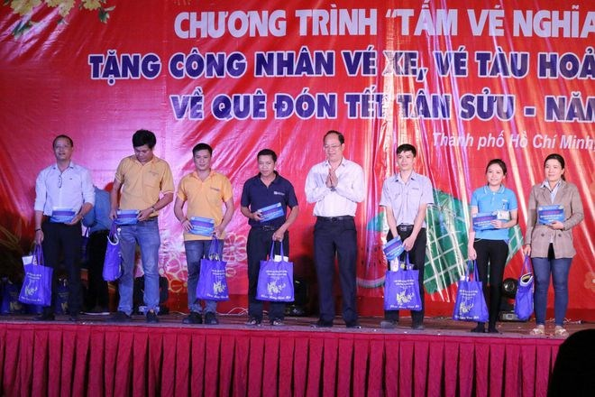 Ông Nguyễn Hồ Hải, Phó bí thư Thành uỷ TP.HCM trao vé máy bay người lao động tại chương trình. Ảnh: PHẠM THU NGÂN