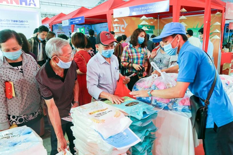 Người dân đi mua gạo bằng phiếu mua hàng miễn phí do UBND quận 3 hỗ trợ - Ảnh: THẢO LÊ