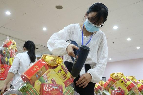 Đinh Lê Quỳnh Như làm thêm tết tại một siêu thị. Trong ảnh: Như đang sấy màng co các giỏ quà tết để giúp bao bì căng bóng, đẹp mắt - Ảnh: BÌNH MINH