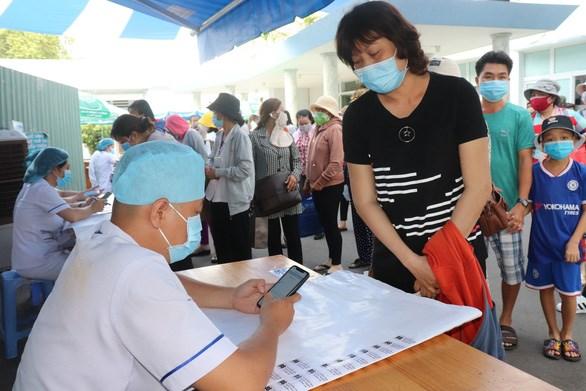 Nhân viên y tế hỗ trợ người bệnh khai báo y tế điện tử tại Bệnh viện Ung bướu TP.HCM (cơ sở 1) - Ảnh: XUÂN MAI