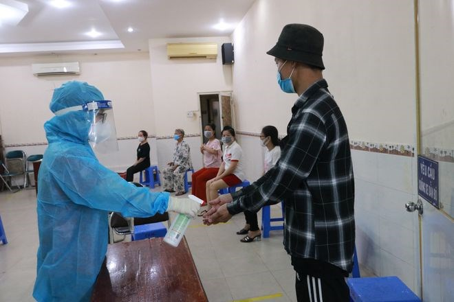 Tiểu thương được xịt khuẩn bàn tay trước khi vào lấy mẫu. Ảnh: Nhật Linh