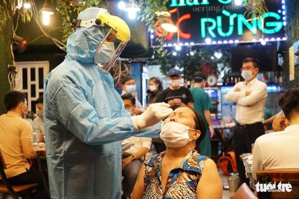 Nhân viên y tế lấy mẫu xét nghiệm tại một quán nhậu ở P.11, quận Bình Thạnh. Ảnh: Đan Tuấn