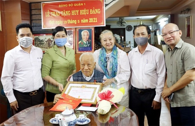 Lãnh đạo Quận 1 trao tặng Huy hiệu 75 năm tuổi Đảng cho đảng viên Trần Đình Bút.(Ảnh: thanhuytphcm.vn)