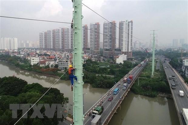 Công nhân Tổng Công ty Điện lực Thành phố Hồ Chí Minh thi công trồng trụ điện trên đường Đồng Văn Cống. (Ảnh: TTXVN)