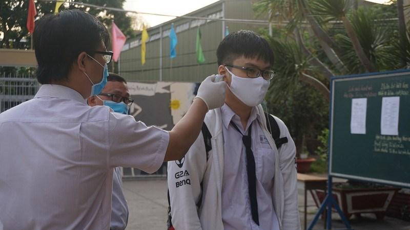 Giáo viên Trường THPT Phú Nhuận, quận Phú Nhuận đo thân nhiệt cho học sinh trong ngày đầu trở lại trường sau kỳ nghỉ dài tránh dịch. Ảnh: NQ
