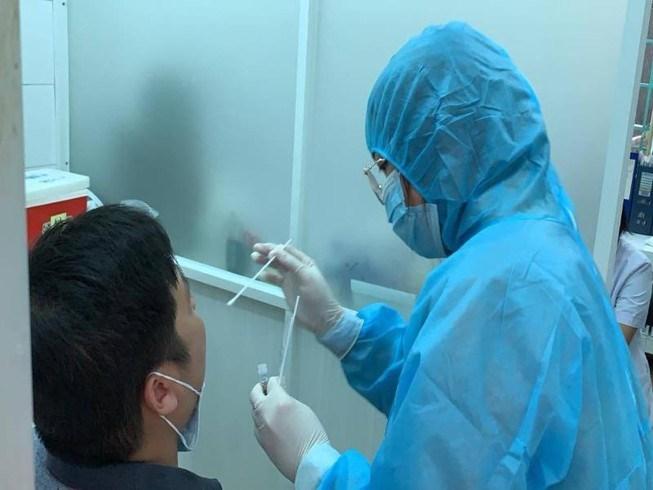 Nhân viên Trung tâm Y tế Quận 3 đang lấy mẫu xét nghiệm người đi từ Đà Nẵng về TP.HCM từ ngày 1/7. Ảnh: HL