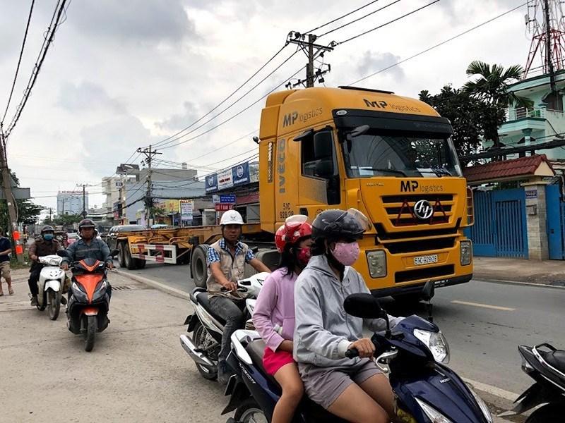 Người đi xe máy phải leo lên lề để tránh xe container. Ảnh: ĐÀO TRANG