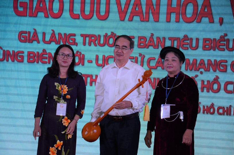 Phó Chủ tịch Uỷ ban MTTQ Việt Nam tỉnh Cao Bằng Đặng Thị Duyên tặng cây đàn tính - biểu trưng văn hóa đặc trưng của các dân tộc ở tỉnh Cao Bằng cho Bí thư Thành ủy TPHCM Nguyễn Thiện Nhân. Ảnh: Long Hồ