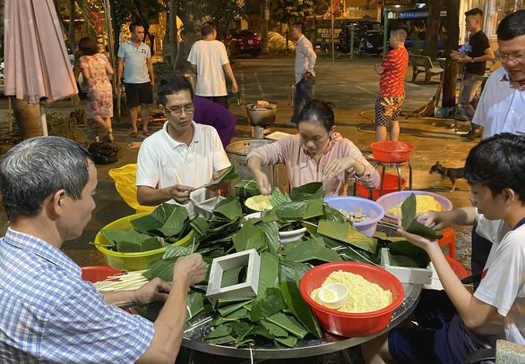 Ngay từ chiều, đông đảo người dân xóm công viên Hạnh Phúc đã tập hợp để gói bánh chưng - Ảnh: THẢO LÊ