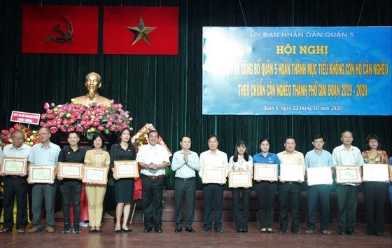 Bí thư Quận ủy quận 5 Nguyễn Văn Hiếu và Giám đốc Sở LĐ-TB-XH Lê Minh Tấn trao giấy khen cho các tập thể , cá nhân có đóng góp tích cực trong thực hiện mục tiêu không còn hộ cận nghèo chuẩn giai đoạn 2019-2020. Ảnh: MAI HOA
