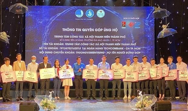Đại diện các tổ chức, doanh nghiệp, đơn vị trao bảng tượng trưng số tiền ủng hộ miền Trung cho Ban tổ chức. (Ảnh: Hồng Giang/TTXVN)