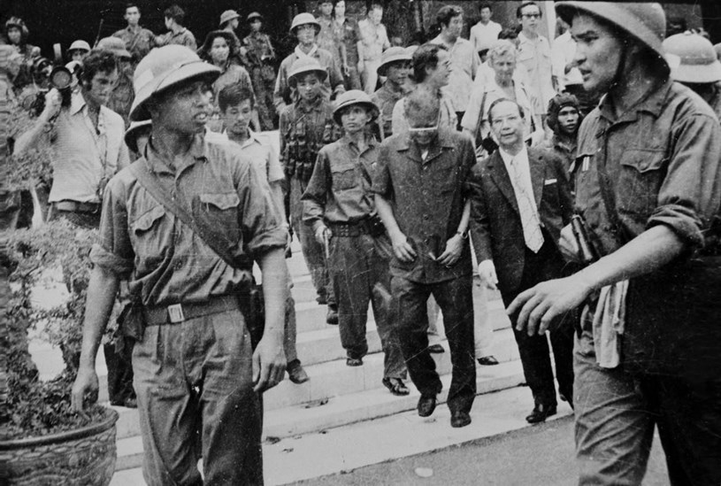 Đại úy Phạm Xuân Thệ (bên phải), Trung đoàn phó Trung đoàn 66, Sư đoàn 304 (Quân đoàn 2) cùng các chiến sỹ Quân giải phóng dẫn giải Tổng thống Dương Văn Minh và Thủ tướng Vũ Văn Mẫu của Ngụy quyền Sài Gòn tới Đài Phát thanh để đọc lời tuyên bố đầu hàng vô điều kiện, trưa 30/4/1975. (Ảnh: TTXVN)
