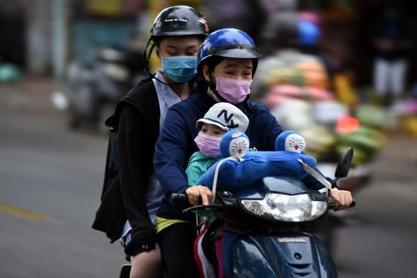 Trẻ em ra đường được trang bị áo ấm, khẩu trang kỹ càng - Ảnh: LÊ PHAN