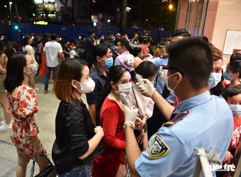 Người dân được anh bảo vệ hai tay hai nhiệt kế điện tử đo thân nhiệt và nhắc đeo khẩu trang khi ra vào trung tâm thương mại Takashimaya (Q.1, TP.HCM) - Ảnh: NGỌC PHƯỢNG